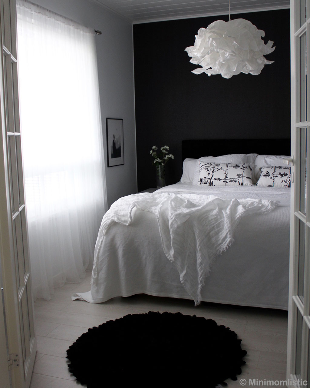 bed with white bed sheet round black kids rugs